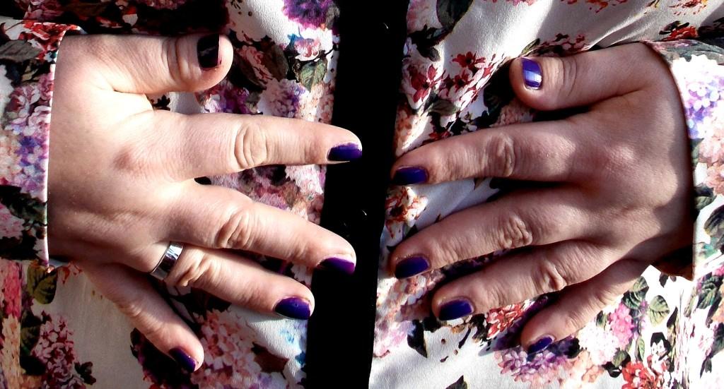Mollige Damenhände vor Blümchenbluse