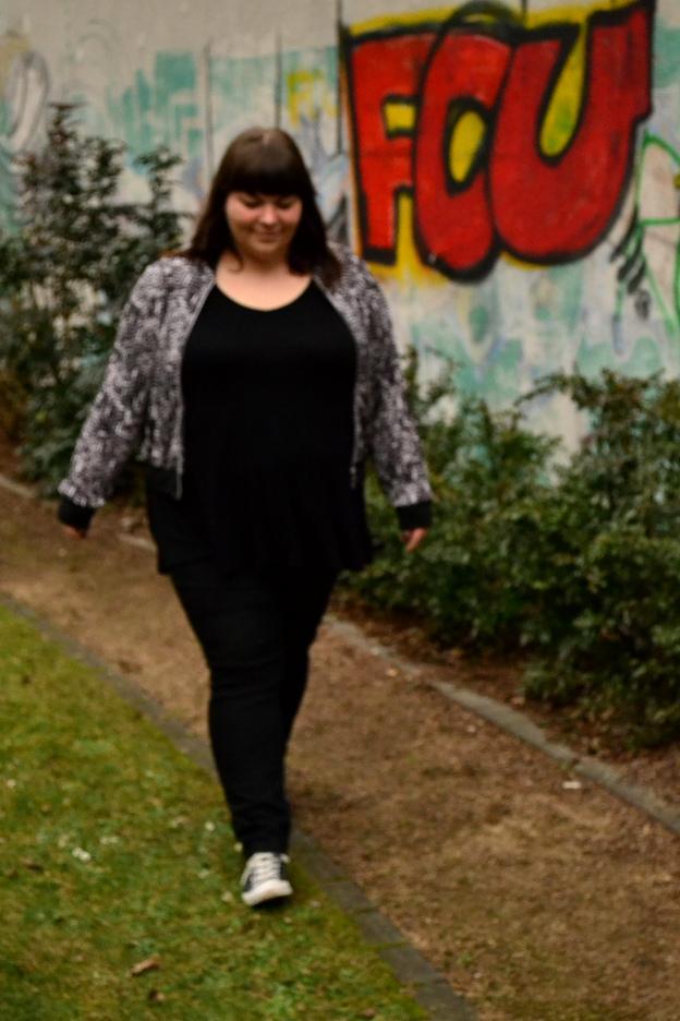 Schwarz-weißer Plus Size Blouson vor einem Graffiti in Berlin